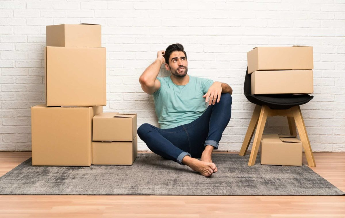 a guy next to a moving boxes